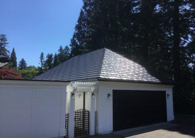 Cedar shake black metal roof on white house through back entrance