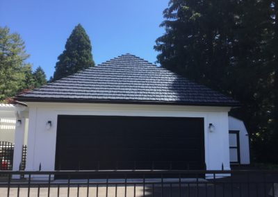 Black metal slate roof on garage on a white house